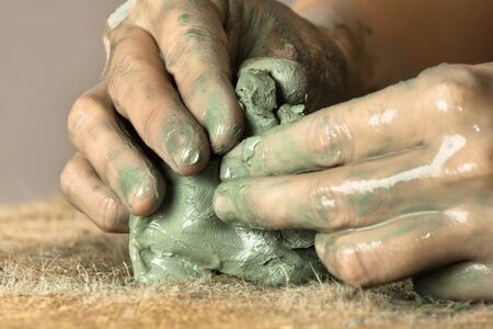 moulding: hands of woman moulding blue clay on the burlap