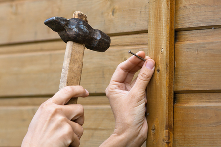 Clouseup de mains martelant le clou dans la planche Banque d'images - 67076123
