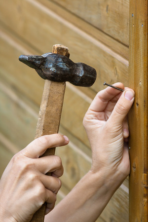 hands hammering nail in wooden plank, closeup