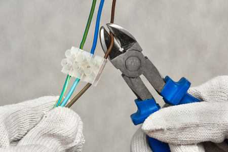 clippers: hands of electrician cutting wires with clippers Stock Photo