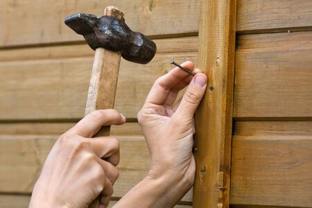 clouseup of hands hammering nail in wooden plank - construction concept