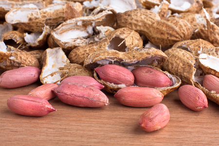 earthnut: heap of raw peeled peanut among shells on the table, closeup
