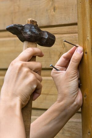 hammering a nail. hands hammering nail in plank of wooden house during repair photo a