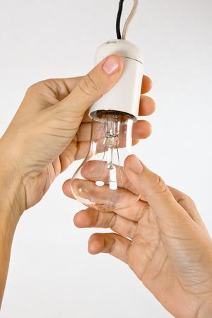 enchufe de luz: manos cambiar la bombilla de luz incandescente en el zócalo Foto de archivo