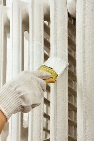 hand painting white radiator central heating with brush