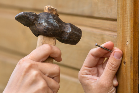 clouseup of hands hammering nail in wooden plank