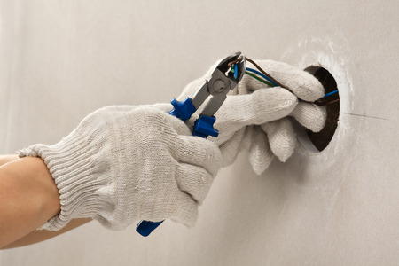 hands of electrician in gloves cutting wires with clippers Stock Photo