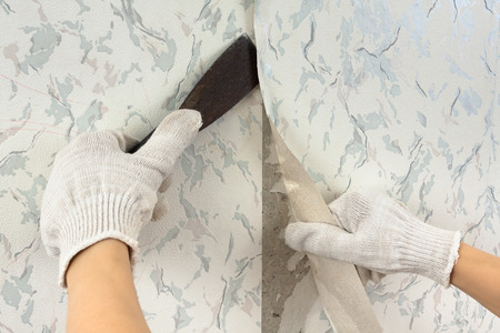 hands in glove removing old wallpaper with spatula during repair