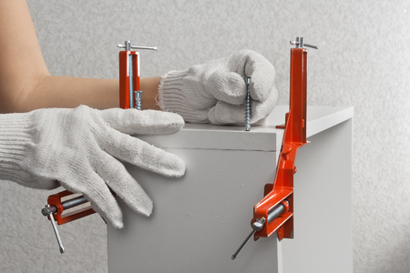 新しい家具の部品を組み立てる大工の手