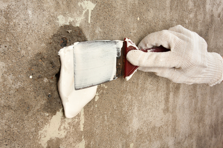 hand plastering surface of wall with spatula during repair