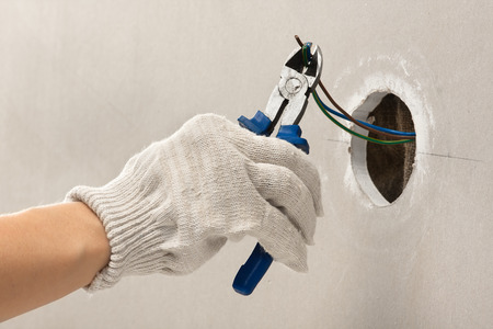hand of electrician in gloves cutting wires with clippers during repair