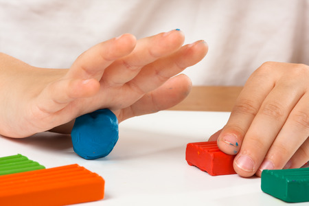 child hands molding from plasticine on the table
