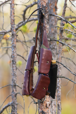 hunting bandoleer and knife hanging on the tree Stock Photo - 89315618