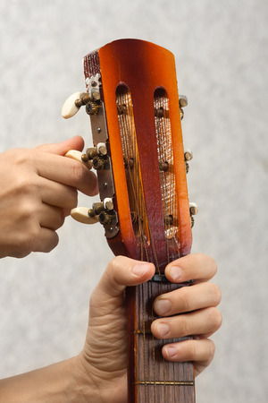 closeup of hands tuning acoustic guitar from headstock Foto de archivo