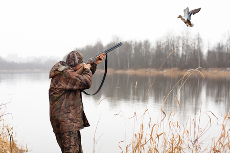 hunter shooting from shotgun to the flying duck Standard-Bild