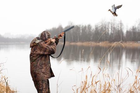 myśliwy strzelający ze strzelby do latającej kaczki
