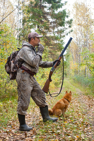 hunter with a grouse call in the forest
