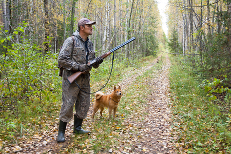 hunter with dog on the forest road during autumn hunt