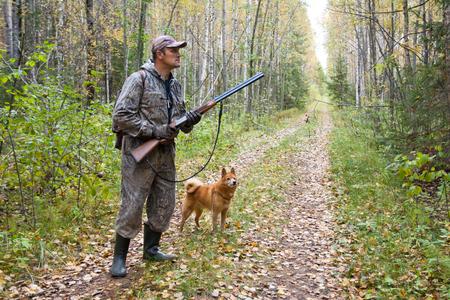 myśliwy z psem na drodze leśnej podczas polowania jesienią