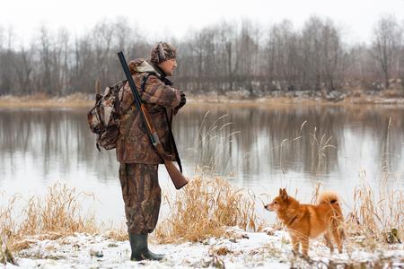 jager met jachtgeweer en hond op de rivieroever