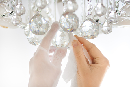 closeup of hands cleaning the chandelier with rag Banco de Imagens