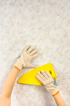 Hands in gloves smoothing wallpaper with spatula on the wall during repair. There is a place for your text in the top of picture.