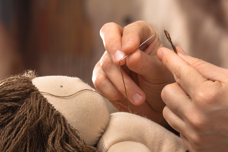 hands of woman sewing hair to the Waldorf doll, closeup