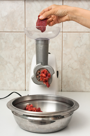 hand of woman making forcemeat with meat grinder in the kitchen 免版税图像