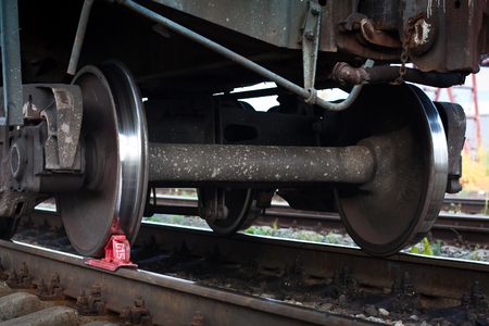 red railway brake shoe under the train wheel on the rails