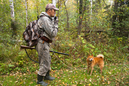 hunter with a dog beckons hazel hen on a forest glade through a call Stockfoto