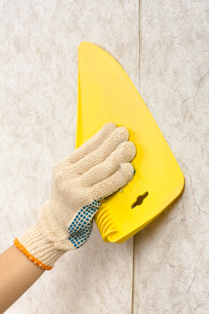 hand smoothes wallpaper with a plastic spatula on the wall during repair