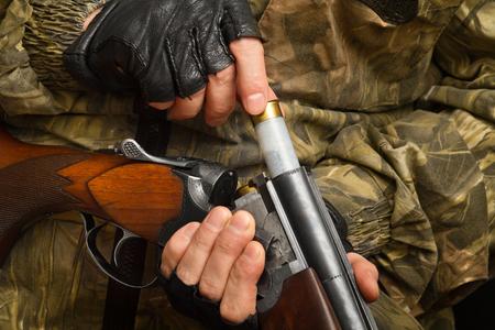 the hunter inserts the cartridge into the double-barrel shotgun