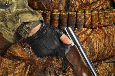 the hand of the hunter in glove holding an unloaded double-barreled shotgun 写真素材