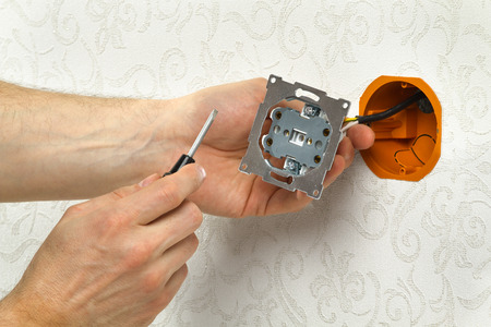hands of an electrician install the power outlet on the wall
