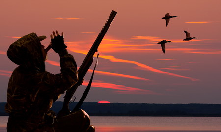 the hunter lures waterfowl using duck call at sunset