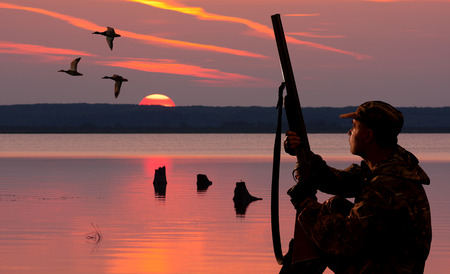 silhouettes of a waterfowler at sunset background on body of water