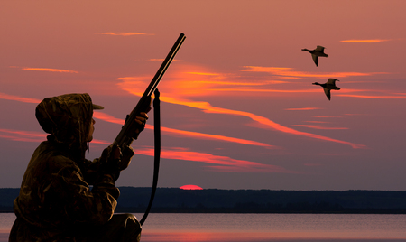 silhouette of a duck hunter at sunset background on body of water