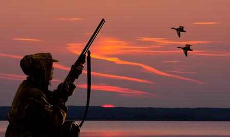 sylwetka łowcy kaczek na tle zachodu słońca na zbiorniku wodnym