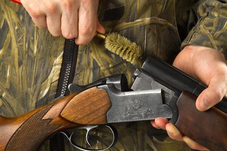 hunter cleans the barrels of his shotgun with a ramrod, closeup Banco de Imagens