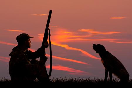 Silhouetten eines Jägers und eines Hundes, die bei Sonnenuntergang auf der Jagd sitzen