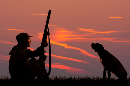 sylwetki myśliwego i psa, którzy siedzą na tle zachodu słońca na polowaniu