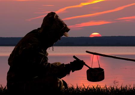 sylwetka myśliwego jedzącego obiad przed zachodem słońca nad jeziorem