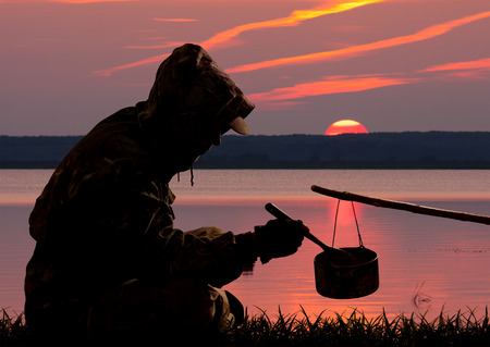 the silhouette of a hunter who dines against the sunset on the lake