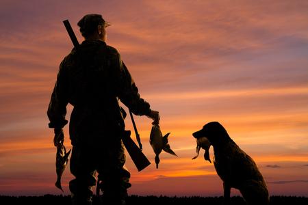 silhouetten van de eendenjager en zijn hond met prooi op de zonsondergangachtergrond Stockfoto