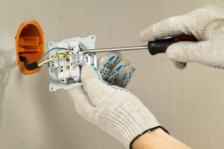 a person with a screwdriver in his hands connects an electrical outlet to the network, close up
