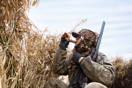the duck hunter sits in the blind of the reeds and lures the ducks Reklamní fotografie