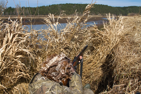 duck hunter aims a shotgun hiding in a blind of reeds on the shore Standard-Bild