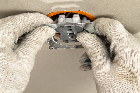 hands of an electrician inserts a power outlet into the socket box on the plasterboard wall Фото со стока