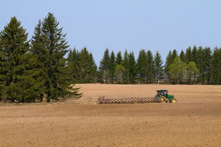 tractor with harrow working on the ploughed field in the spring
