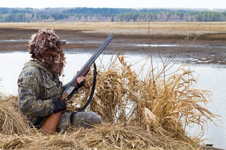 duck hunter with a shotgun climbs out of the hunting blind of reeds on the lake